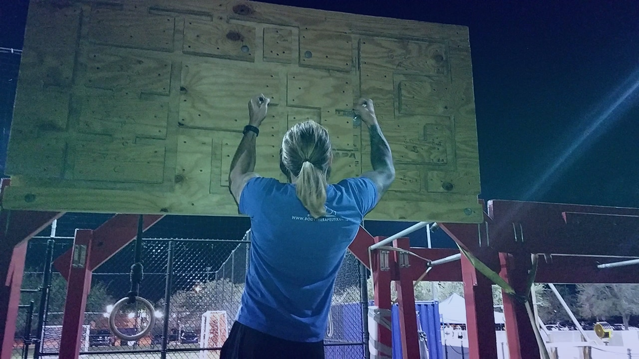 Man climbing peg maze board American ninja warriors